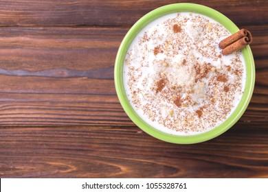 Brazilian sweet winter festival dessert Canjica. White corn porridge with cinnamon and coconut. Selective focus. Top view.
