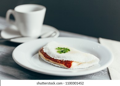 Brazilian Tapioca with cheese (coalho) and coffee over a wooden table