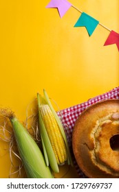 "Brazilian typical corn cake, tablecloth, corn cob and colorful flags june party ""festa junina"" yellow background frame"