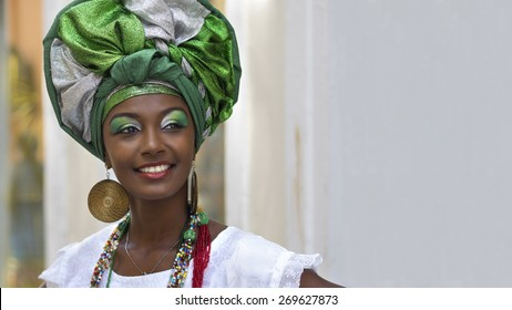 Brazilian woman of African descent, smiling, dressed in traditional Baiana attire in Pelourinho, Salvador, Bahia, Brazil.
