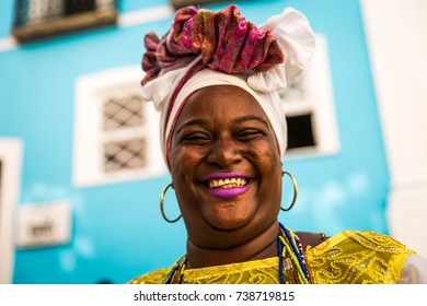 Brazilian woman of African descent, smiling, dressed in traditional Baiana attire in Pelourinho, Salvador, Bahia, Brazil