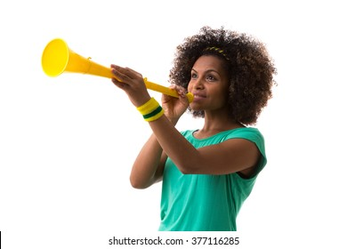 Brazilian woman blowing by vuvuzela on white background