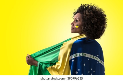 Brazilian woman holding the Brazilian flag on yellow background