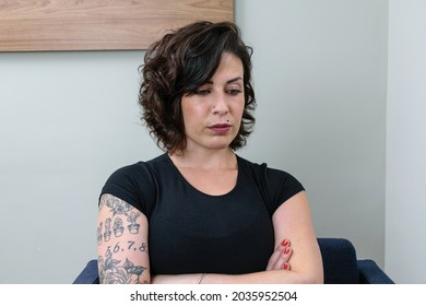Brazilian woman, tattooed, with arms crossed and looking down. Thoughtful and upset.