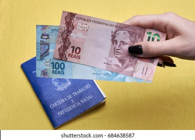 Brazilian work books or document work, social security or worker rights (Carteira de trabalho e Previdencia Social) on the yellow Brazilian flag with hand holding money notes.