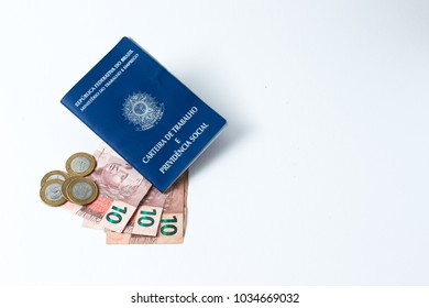 Brazilian work document and social security document (carteira de trabalho) with money as a concept of how little money the worker made  on white background - Copy Space - Top View
