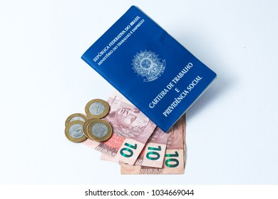 Brazilian work document and social security document (carteira de trabalho) with money as a concept of how little money the worker made  on white background - Top View