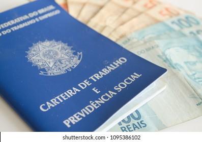 A brazilian working permit (carteira de trabalho) with some real brazil money bills