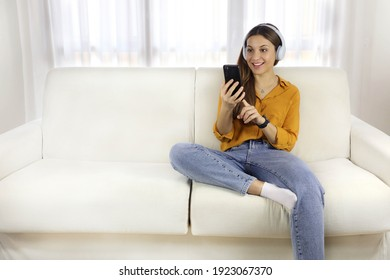 Brazilian young woman listening to music with mobile phone while sitting on sofa at home. Copy space.