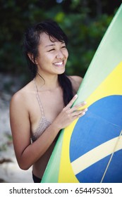 Brazilian-Japanese surfer girl with a surf board showing the Brazilian flag