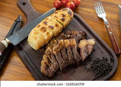 Brazilizan Barbecue slice of striploin and garlic bread