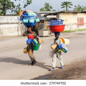 Brazzaville, Republic of Congo - May 1st, 2012: An African woman and child in Brazzaville the capital of the Republic of Congo carrying plastic water buckets on their heads.