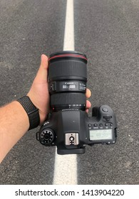 Brcko district, Bosnia and Herzegovina - May 21th 2019: Man standing on road, holding Canon EOS 6D camera with Canon 16-35 f4 L lens on it