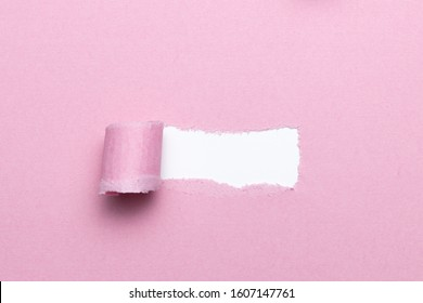 Breach or pealed of paper for hidden text used as template or mockup on pink natural paper