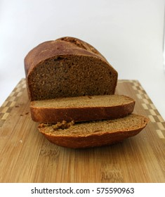 breack loaf of black wholegrain malt, rye and wheat bread  with two pieces on wooden cutting board