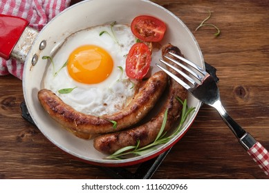 Breackfast with fried eggs, sausages and tomatoes