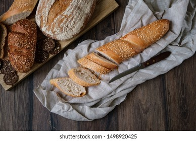 Bread. Assortment of different types of bread. Sliced ​​bread on a wooden background. Loaf, bun, baguette, cereal bread. Bakery products.