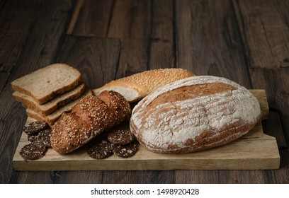 Bread. Assortment of different types of bread. Sliced bread on a wooden background. Loaf, bun, baguette, cereal bread. Bakery products.