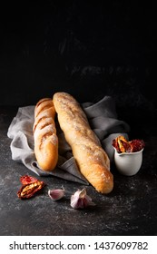 Bread baguettes on the grey cotton napkin on dark background