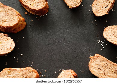 Bread bakery art. Food composition. Wholegrain slices frame on black background.