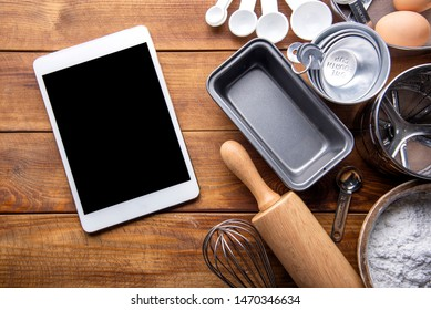 bread bakery ingredients with kitchenware and tablet on wooden table. flat lay top view