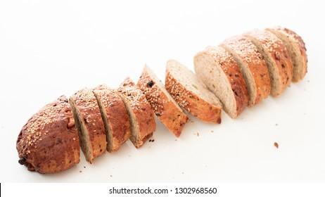 Bread baking recipe. Healthy nutrition. Sliced wholegrain baguette on white background.