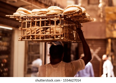 Bread basket in a head of a person riding the bicycle in Cairo, Egypt