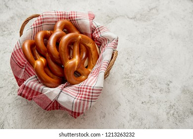 Bread basket with red and white checkered napkin filled with fresh brown pretzels. Top view. Placed on stone table.
