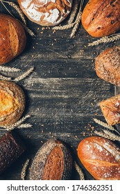 Bread border on wood background with copy space. Whole grain loaves with spikelets. Different types of bread arranged as frame. Bakery, cooking and grocery store concept.