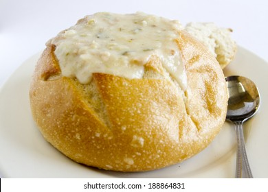 A bread bowl filled with clam chowder.