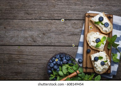 bread with bran, berries on a wooden board on a wooden background