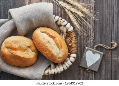Bread buns in basket on rustic wood with wheat ears and wooden heart tag, top view