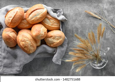 Bread buns in basket on rustic wood with wheat ears, top view on grey textured background