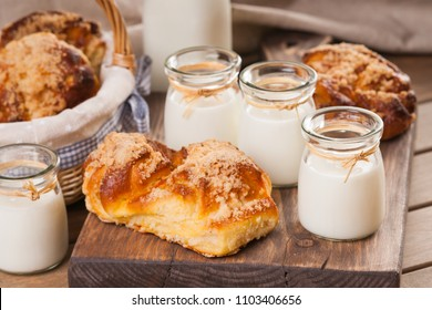Bread buns and jars with milk on a cutting board
