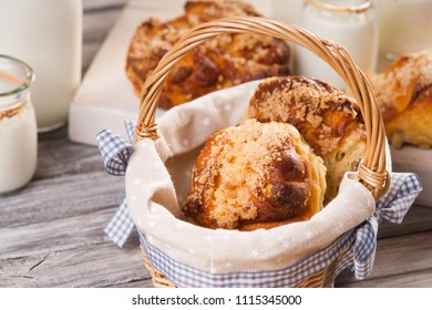 Bread buns in wicker basket and jars with milk