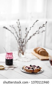 Bread with butter and blackberry jam on white table at home. Willow branches in the vase.