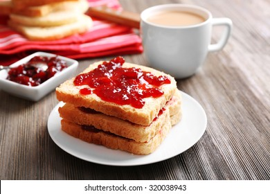 Bread with butter and homemade jam on wooden table, closeup