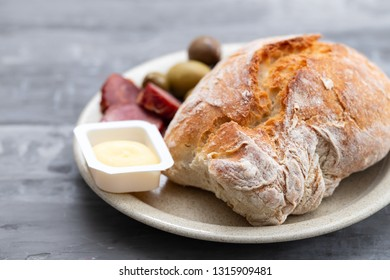 bread with butter, olives and smoked sausage on dish on ceramic background