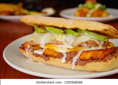 Bread chapata breakfast with egg, fried cheese, beans and avocado on a white plate.