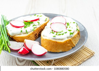 Bread with cheese spread, chives and radishes. healthy breakfast concept.
