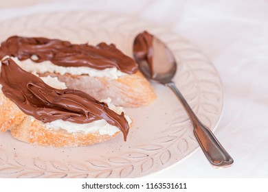 Bread with chocolate cream and mascarpone cheese. A dirty spoon on the plate.