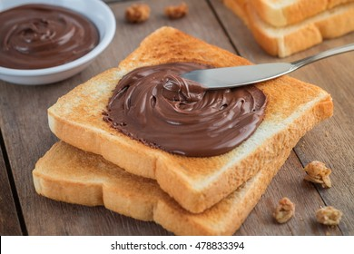 Bread with chocolate cream on wooden table