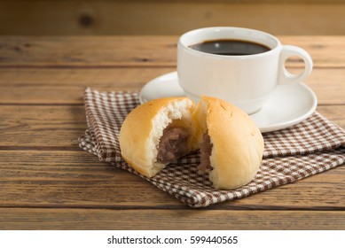 Bread with coffee cup on wood table.
