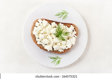 Bread with curd cheese and dill on white plate, top view