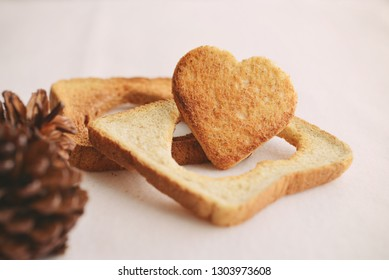 Bread cut in the shape of hearts on the white bed, with dried flowers. Concept about love and relationship.Valentine idea for design work with copy space.Love preparation from heart.Homemade cooking.