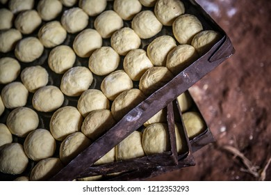 bread dough in balls on old metal trays rising waiting to be cooked