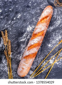 bread and ears of wheat on wooden background
