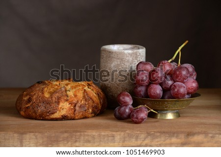 Bread, grapes and wine cup on wooden vintage table