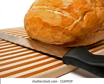 Bread and knife on cutting board, white background