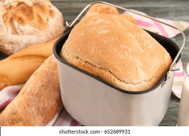 Bread machine pan with freshly baked loaf on table